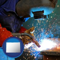 colorado an industrial welder wearing a welding helmet and safety gloves