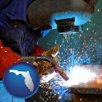 florida an industrial welder wearing a welding helmet and safety gloves