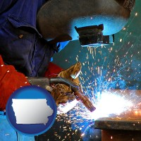 iowa an industrial welder wearing a welding helmet and safety gloves