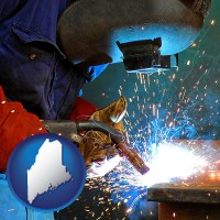 maine an industrial welder wearing a welding helmet and safety gloves