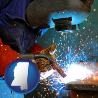 mississippi an industrial welder wearing a welding helmet and safety gloves