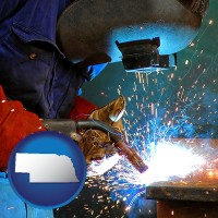 nebraska an industrial welder wearing a welding helmet and safety gloves