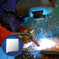 new-mexico an industrial welder wearing a welding helmet and safety gloves