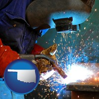 oklahoma an industrial welder wearing a welding helmet and safety gloves