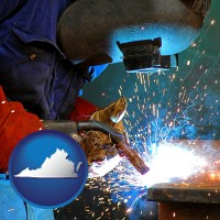 virginia an industrial welder wearing a welding helmet and safety gloves