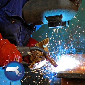 an industrial welder wearing a welding helmet and safety gloves - with Massachusetts icon