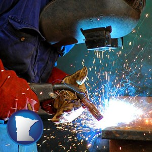 an industrial welder wearing a welding helmet and safety gloves - with Minnesota icon