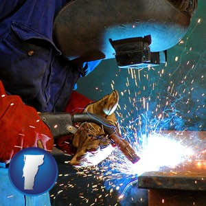 an industrial welder wearing a welding helmet and safety gloves - with Vermont icon